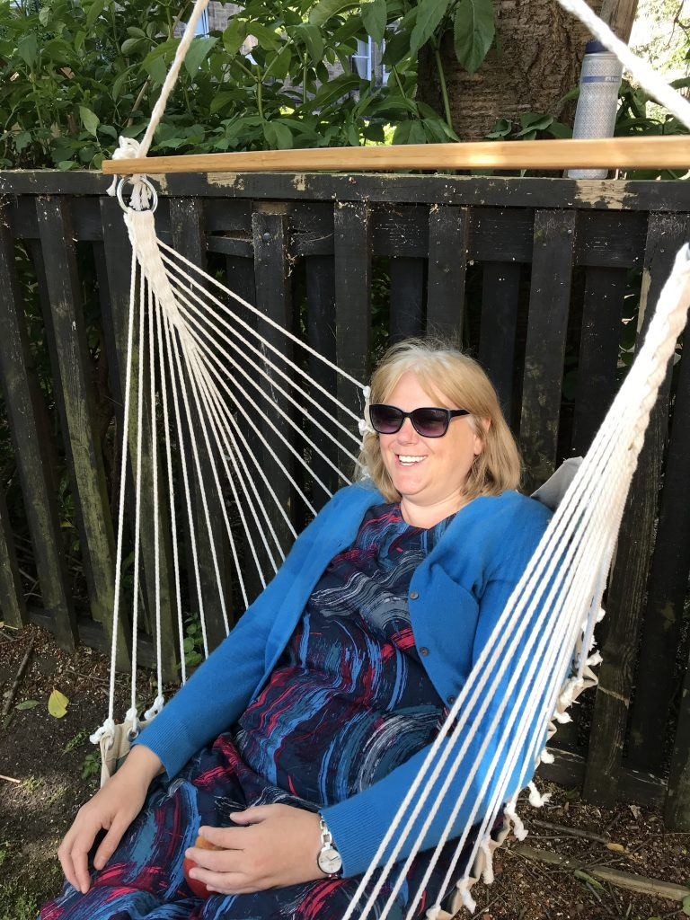 Lesley sitting in a swinging tree chair.