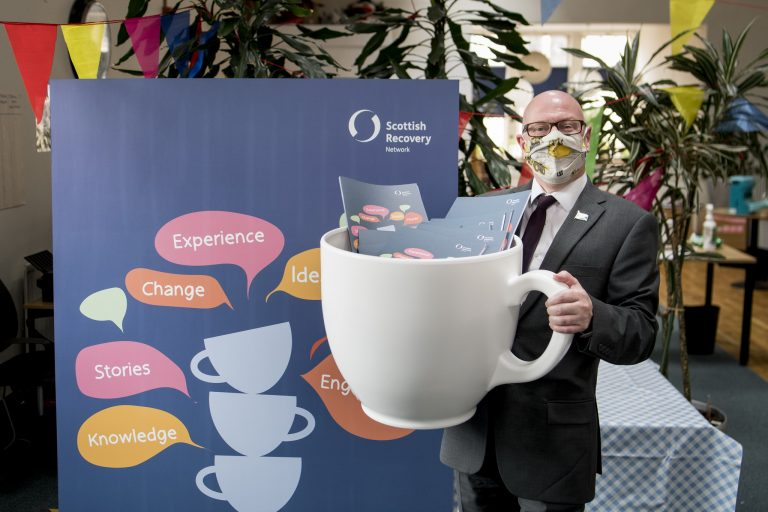 Photo of Minister for Mental Wellbeing and Social Care with a giant teacup.
